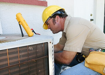an air conditioning repairman working on a compressor unit.